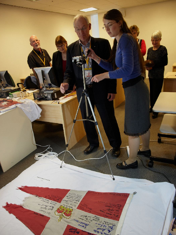Museum volunteers standing around a camera on a tripod photographing a torn red and white flag with signatures on it